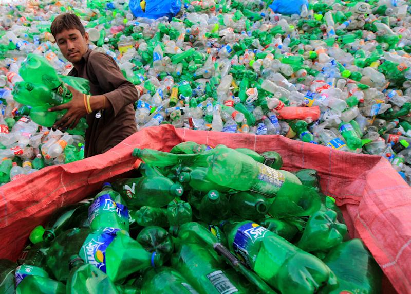 A worker sorts plastic bottles at a recycling workshop in Islamabad, Pakistan.  (Caren Firouz / Reuters)