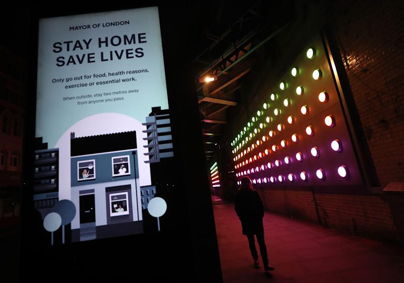 A woman walks between a coronavirus information sign and a light installation near London Bridge, London, as the UK continues in lockdown to help curb the spread of the coronavirus.