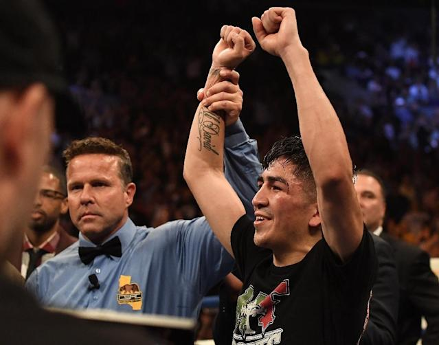 Mexico's Leo Santa Cruz, shown celebrating a victory last year, kept his feathweight title with a unanimous decision victory Saturday (AFP Photo/Jayne Kamin-Oncea)