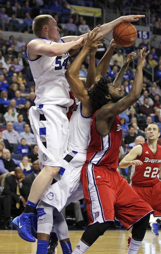 Saint Louis' John Manning (54) and Dwayne Evans (21) compete with Duquesne's Dominique McKoy for a rebound in the second half of an NCAA college basketball game, Thursday, Feb. 27, 2014, in St. Louis. Duquesne defeated Saint Louis 71-64. (AP Photo/Tom Gannam)