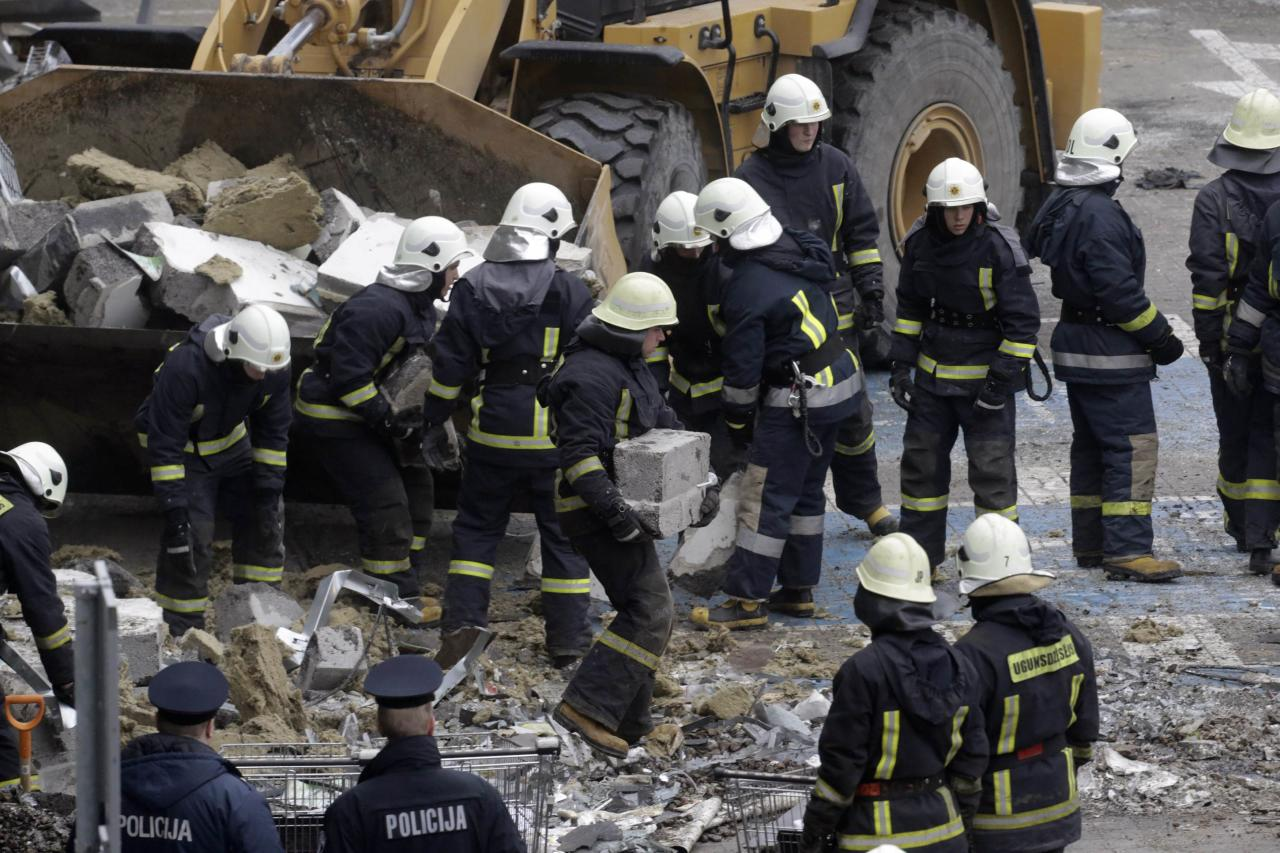 Firefighters remove debris from a collapsed supermarket in capital Riga November 22, 2013. Rescue workers pulled more bodies from the ruins of the collapsed supermarket on Friday, taking the death toll to 32 with others feared buried in the rubble. REUTERS/Ints Kalnins (LATVIA - Tags: DISASTER)