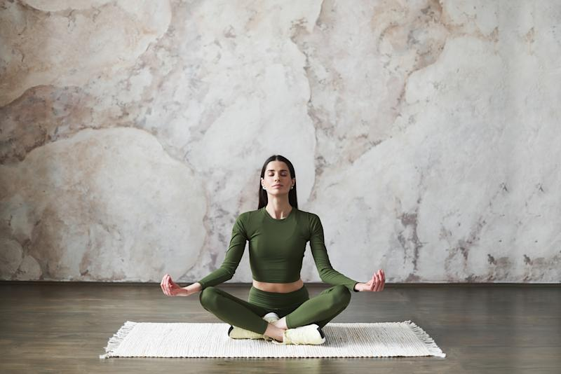 Front view portrait of beautiful young woman with long dark hair wearing sportswear, resting after doing yoga exercises, sitting in ardha Padmasana, Lotus pose, relaxing. Full length. Wellness concept