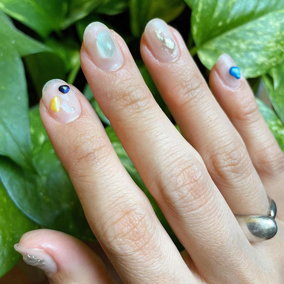 """<p>Higuchi channeled her love of finding tiny stones at the beach or bead shops everywhere she goes into this earthy 3D jelly nail look. """"I thought even <a href=""""https://www.allure.com/story/nail-art-designs-for-short-nails?mbid=synd_yahoo_rss"""" rel=""""nofollow noopener"""" target=""""_blank"""" data-ylk=""""slk:short nails"""" class=""""link rapid-noclick-resp"""">short nails</a> would look pretty when I put them on my nails,"""" she says — and we couldn't agree more. She combined flat-backed stones with a <a href=""""https://www.allure.com/story/aurora-nails-korean-beauty-nail-art-trend?mbid=synd_yahoo_rss"""" rel=""""nofollow noopener"""" target=""""_blank"""" data-ylk=""""slk:chrome nail technique"""" class=""""link rapid-noclick-resp"""">chrome nail technique</a> most nail artists are now familiar with to make the 3D jelly look like molten metal.</p> <p>At home, you can glue small, clear stones or beads onto nails coated with a sheer white polish, like <a href=""""https://shop-links.co/1742881560529832031"""" rel=""""nofollow noopener"""" target=""""_blank"""" data-ylk=""""slk:JinSoon's Dew"""" class=""""link rapid-noclick-resp"""">JinSoon's Dew</a>, to imitate Higuchi's creation, she recommends. Seal them in with a gel-like topcoat, such as the Best of Beauty-winning <a href=""""https://shop-links.co/1742881654422240862"""" rel=""""nofollow noopener"""" target=""""_blank"""" data-ylk=""""slk:Essie Gel-Setter"""" class=""""link rapid-noclick-resp"""">Essie Gel-Setter</a>. </p>"""