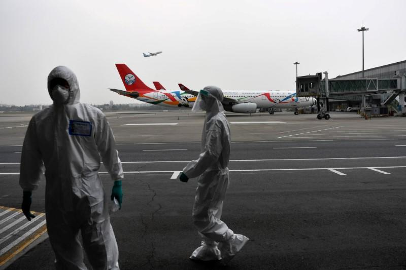 Customs officers in protective suits are seen near a Sichuan Airlines aircraft on the tarmac of Chengdu Shuangliu International Airport