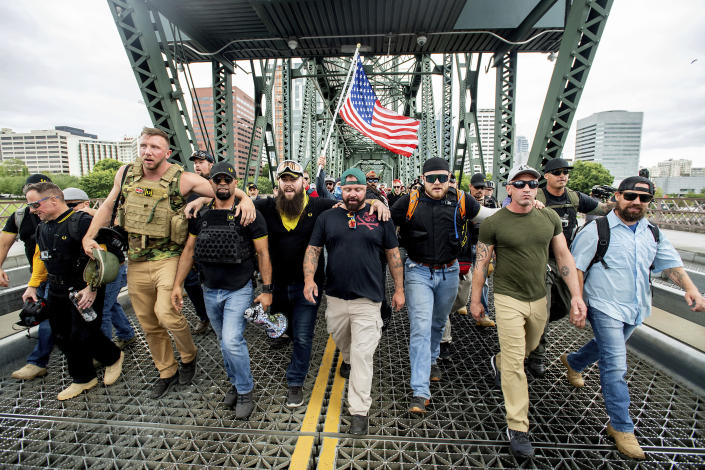 """Members of the Proud Boys and other right-wing demonstrators march across the Hawthorne Bridge during an """"End Domestic Terrorism"""" rally in Portland, Ore., on Saturday, Aug. 17, 2019. The group includes organizer Joe Biggs, center in green hat, and Proud Boys Chairman Enrique Tarrio, holding megaphone. (AP Photo/Noah Berger)"""