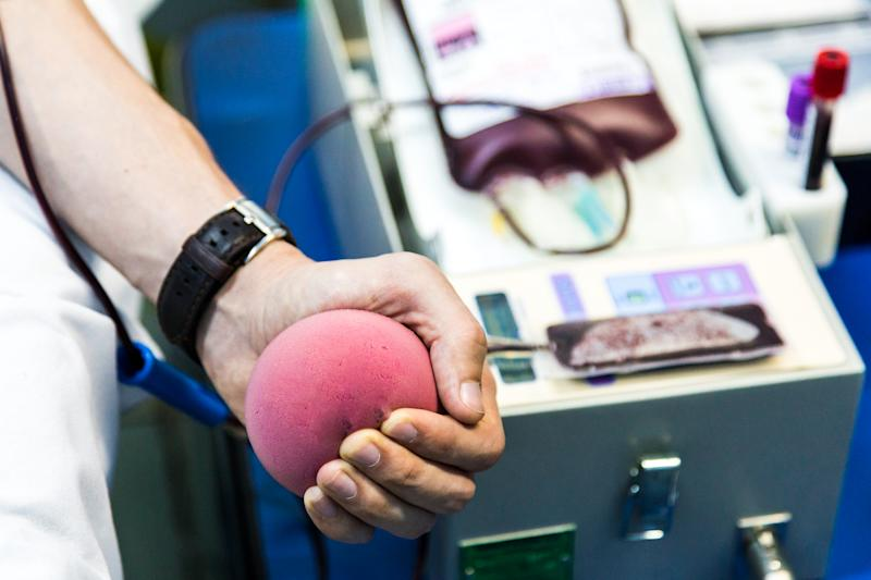 Color image depicting a blood donor in the process of donating blood in a medical clinic. Focus on the donor's arm and they are squeezing a foam ball to help the blood flow quicker. Room for copy space.