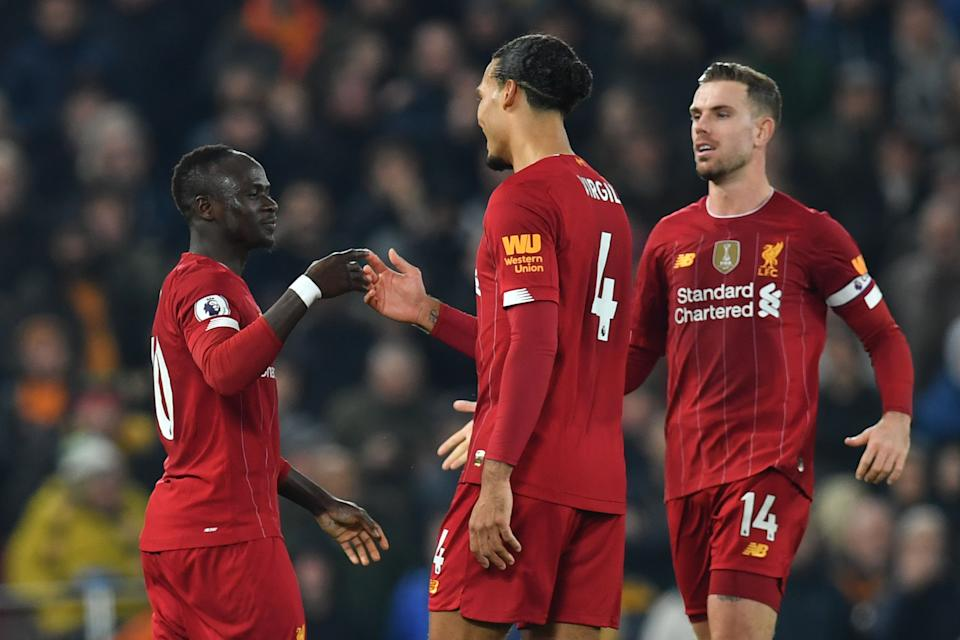 Liverpool's Senegalese striker Sadio Mane (L) celebrates with Liverpool's Dutch defender Virgil van Dijk (C) and Liverpool's English midfielder Jordan Henderson (R) after scoring the opening goal during the English Premier League football match between Liverpool and Wolverhampton Wanderers at Anfield in Liverpool, north west England, on December 29, 2019. (Photo by Paul ELLIS / AFP) / RESTRICTED TO EDITORIAL USE. No use with unauthorized audio, video, data, fixture lists, club/league logos or 'live' services. Online in-match use limited to 120 images. An additional 40 images may be used in extra time. No video emulation. Social media in-match use limited to 120 images. An additional 40 images may be used in extra time. No use in betting publications, games or single club/league/player publications. /  (Photo by PAUL ELLIS/AFP via Getty Images)