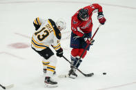 Boston Bruins center Charlie Coyle (13) tangles up Washington Capitals right wing Tom Wilson (43) during the second period of Game 2 of an NHL hockey Stanley Cup first-round playoff series Monday, May 17, 2021, in Washington. (AP Photo/Alex Brandon)