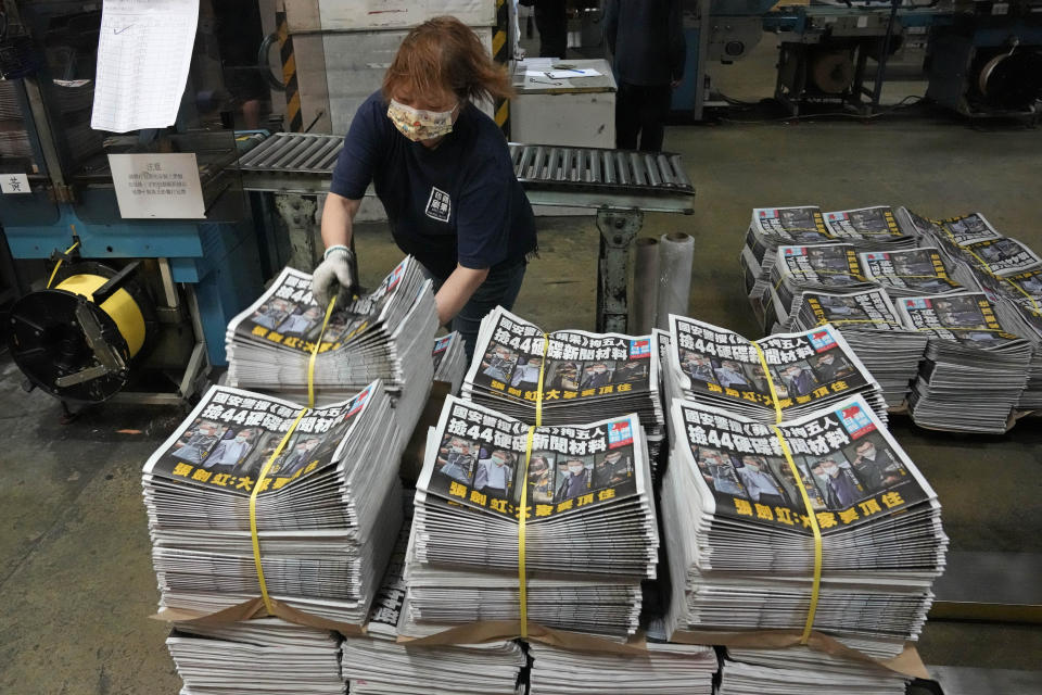 A worker packs copies of Apple Daily newspaper at the printing house in Hong Kong, early Friday, June 18, 2021. Five editors and executives at pro-democracy Apple Daily newspaper were arrested Thursday under Hong Kong's national security law, its stock was halted and police were searching its offices in moves raising concerns about the media's future in the city. (AP Photo/Kin Cheung)