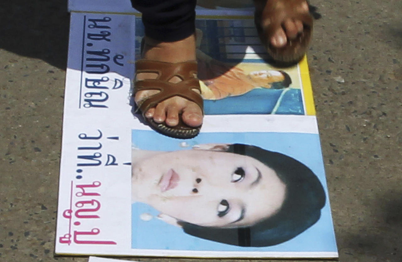 An anti-government protester steps on a poster with the photos of outsted Prime Ministers Thaksin Shinawatra, back, and Yingluck Shinawatra, front, during a rally at the compound of the National Broadcasting of Thailand (NBT) office Friday, May 9, 2014 in Bangkok, Thailand. Thai police fired tear gas and water cannons Friday to push back hundreds of protesters trying to force their way into a government compound, the latest indication that ousting the premier will not solve the country's tense political crisis. (AP Photo/Apichart Weerawong)