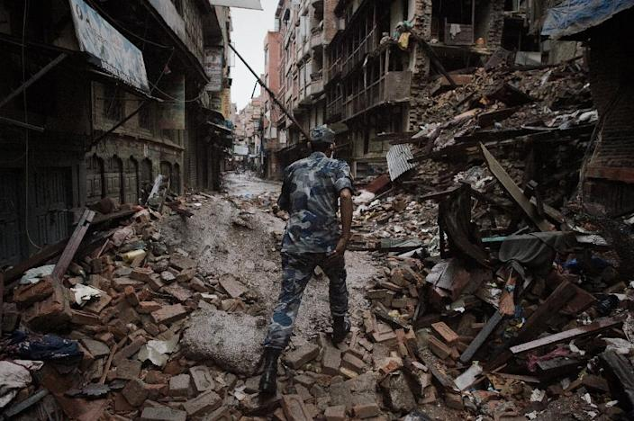 A member of the Nepalese security forces walks among earthquake debris in Kathmandu, on April 28, 2015 (AFP Photo/Nicolas Asfouri)