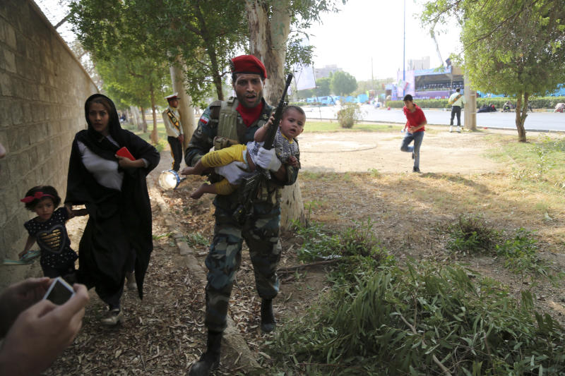 In this photo provided by Mehr News Agency, an Iranian army member carries away a child from a shooting scene during a military parade marking the 38th anniversary of Iraq's 1980 invasion of Iran, in the southwestern city of Ahvaz, Iran, Saturday, Sept. 22, 2018. Gunmen attacked the military parade, killing at least eight members of the elite Revolutionary Guard and wounding 20 others, state media said. (AP Photo/Mehr News Agency, Mehdi Pedramkhoo)