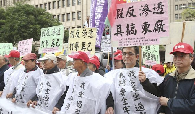 Protesters hold slogans against the anti-infiltration bill outside the legislature in Taipei on Tuesday. Photo: AP