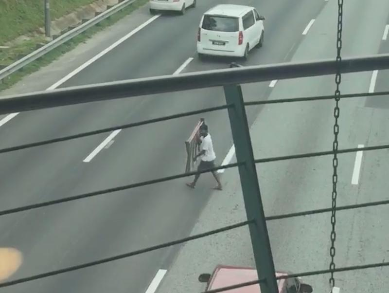 The man leaps into action after spotting the scrap metal lying in the middle of the highway. — Screengrab from Facebook/xidi.zaid