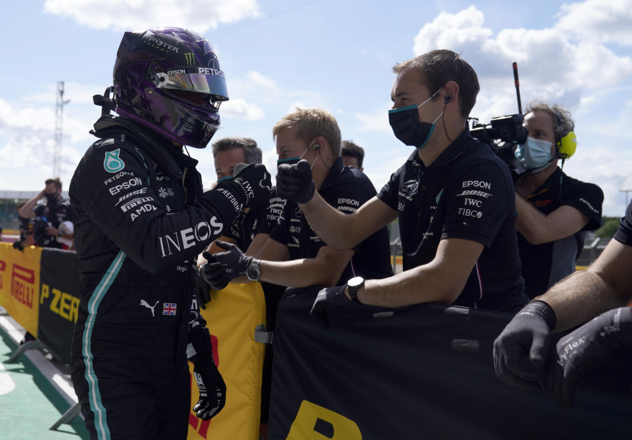 Mercedes driver Lewis Hamilton of Britain, left, celebrates with team members after he clocked the fastest time during the qualifying session for the British Formula One Grand Prix at the Silverstone racetrack, Silverstone, England, Saturday, Aug. 1, 2020. The British Formula One Grand Prix will be held on Sunday. (Will Oliver/Pool via AP)