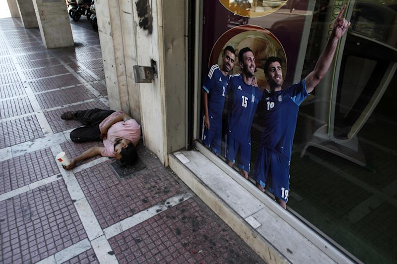 A man begging for alms lays by a sticker with Greece' national football team players one day before general elections in Athens, on Saturday, June 16 2012.  Greeks vote for the second time in six weeks Sunday amid fears that the country could be forced out of the euro if they reject the strict austerity measures taken in return for billions of euros in rescue loans from other European countries and the International Monetary Fund. (AP Photo/Kostas Tsironis)