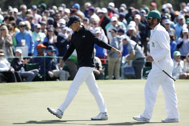 Jordan Spieth of the U.S. hands his putter to his caddie Michael Greller after a birdie on the 9th hole during final round play of the 2018 Masters golf tournament at the Augusta National Golf Club in Augusta, Georgia, U.S. April 8, 2018. REUTERS/Mike Segar
