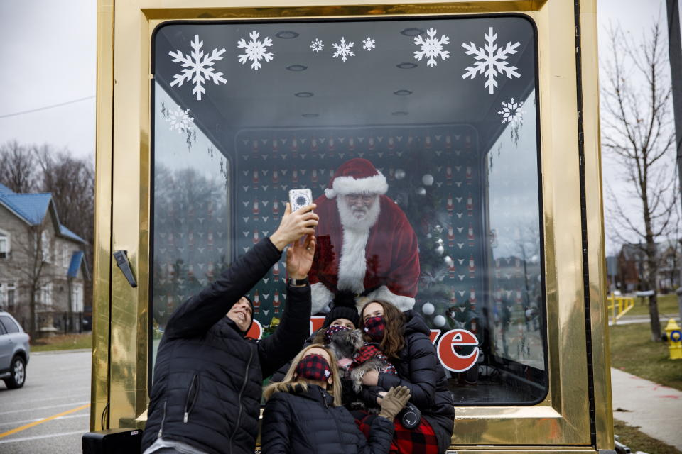 A man dressed as Santa Claus takes photos with families from behind a glass enclosure in Vaughan, Ontario, Sunday, Dec. 13, 2020, after Vaughan Mills cancelled their seasonal in-person visits with Santa amid the continuing COVID-19 pandemic. York Region will go into lockdown starting Monday. (Cole Burston/The Canadian Press via AP)