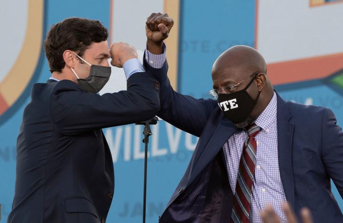 Democratic candidates for Senate Jon Ossoff (L) and Raphael Warnock (R) bump elbows on stage during a rally with US President-elect Joe Biden outside Center Parc Stadium in Atlanta, Georgia, on January 4, 2021. - President Donald Trump, still seeking ways to reverse his election defeat, and President-elect Joe Biden converge on Georgia on Monday for dueling rallies on the eve of runoff votes that will decide control of the US Senate. Trump, a day after the release of a bombshell recording in which he pressures Georgia officials to overturn his November 3 election loss in the southern state, is to hold a rally in the northwest city of Dalton in support of Republican incumbent senators Kelly Loeffler and David Perdue. Biden, who takes over the White House on January 20, is to campaign in Atlanta, the Georgia capital, for the Democratic challengers, Raphael Warnock and Jon Ossoff. (Photo by JIM WATSON / AFP) (Photo by JIM WATSON/AFP via Getty Images)