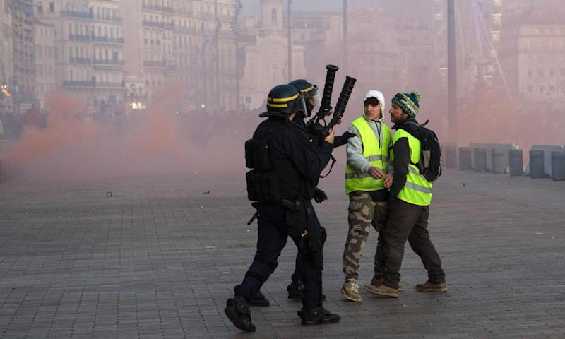 Police confront anti-government activists in Marseilles, where a woman was killed during protests on Saturday.