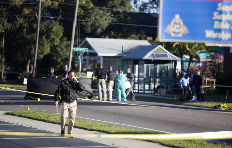 Law enforcement agents investigate a fatal shooting in the Seminole Heights neighborhood in Tampa, Fla., Tuesday, Nov. 14, 2017. Police searched the neighborhood after a person was shot dead, possibly by a serial killer. Spokesman Steve Hegarty said detectives can't immediately say whether the shooting is related to last month's 10-day spree where three people were slain, but officers are treating it like it is. (Jones, Octavio/Tampa Bay Times via AP)