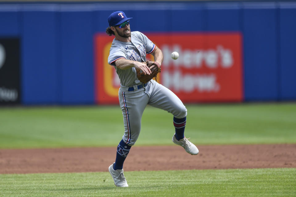 Texas Rangers third baseman Charlie Culberson fields a ground ball hit by Toronto Blue Jays' Marcus Semien who was out at first during the third inning of the first baseball game of a doubleheader in Buffalo, N.Y., Sunday, July 18, 2021. (AP Photo/Adrian Kraus)