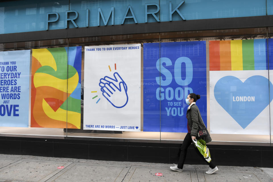 A woman wears a protective mask as she walks past a Primark store in Oxford Street, ahead of the reopening of the non-essential businesses on Monday, June 15, as some of the coronavirus lockdown measures are eased, in London, Friday, June 12, 2020. The British economy shrank by a colossal 20.4% in April, the first full month that the country was in its coronavirus lockdown, official figures showed Friday.(AP Photo/Alberto Pezzali)