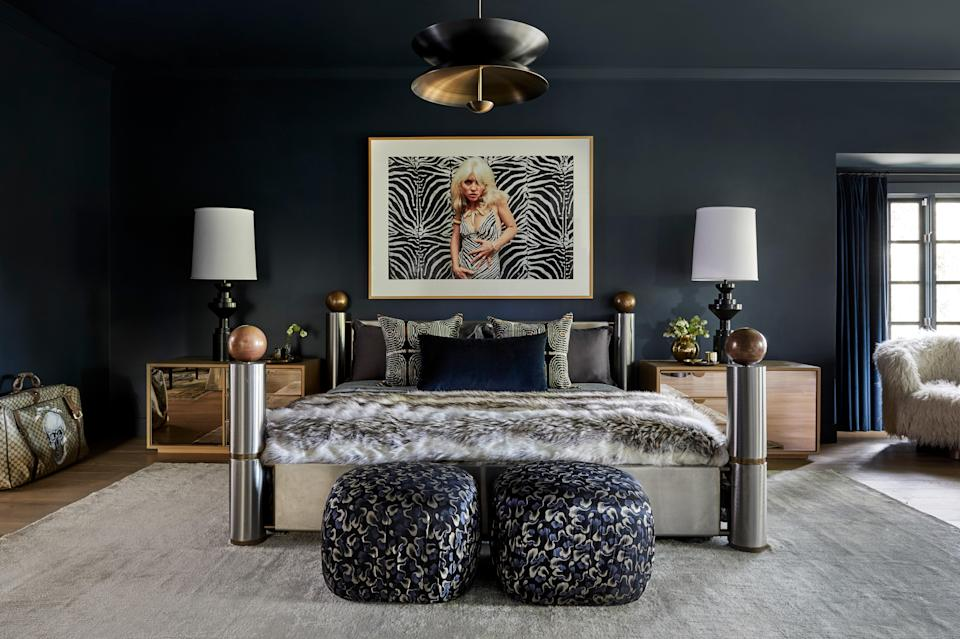 "Miley found her stainless-steel and brass 1980s bed on one of her many scouring expeditions on 1stDibs. ""Miley wanted this room dark and moody,"" says Tish. ""I went with this color paint that I just always love: Blue Note [by Benjamin Moore]. We did the ceiling, the walls, the fireplace, the bookshelves. We did it all."" An iconic image of Debbie Harry photographed by Blondie cofounder Chris Stein hangs above. (Fun fact: Harry tells the story that the zebra-print dress she's wearing in the picture was actually made from a pillowcase her landlord had found in the trash. Ironic then that this shot would hang above another rock star's bedroom pillows four decades later.) An Atelier 001 Regolith pendant light from Garde resonates in moody dark and brass tones. Seating includes a Milo Baughman swivel chair recovered in faux fur and a duo of Karl Springer poufs reimagined in Zak and Fox's Kabuto fabric."