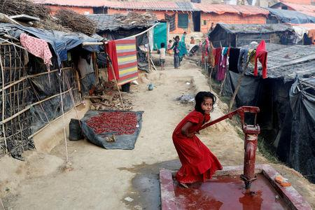 A Rohingya refugee girl plays at a tube-well in Palong Khali camp, near Cox's Bazar, Bangladesh January 14, 2018. REUTERS/Tyrone Siu