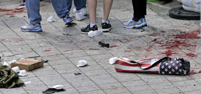 FILE - In this April 15, 2013, file photo, blood from victims covers the sidewalk on Boylston Street, at the site of an explosion during the 2013 Boston Marathon in Boston. At right foreground is a folding chair with the design of an American flag on the cover. A federal grand jury in Boston returned a 30-count indictment against bombing suspect Dzhokhar Tsarnaev on Thursday, June 27, 2013, on charges including using a weapon of mass destruction and bombing a place of public use, resulting in death. (AP Photo/Charles Krupa, File)