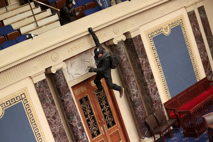 A rioter is seen hanging from the balcony in the Senate Chamber.