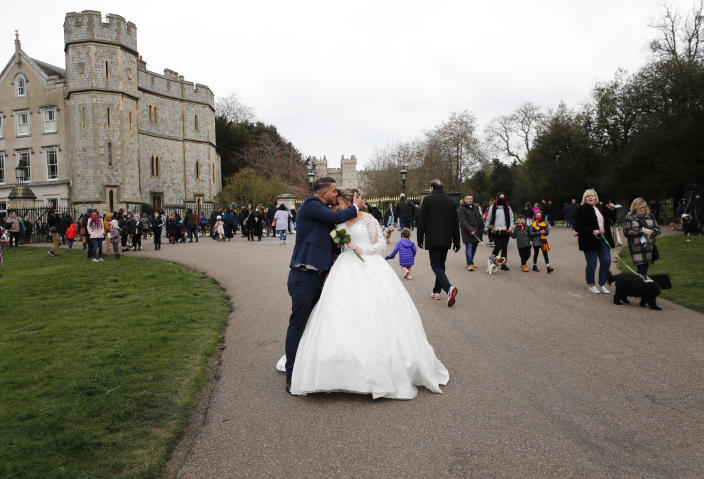A newlywed couple kiss outside the gates of Windsor Castle, a day after the death of Britain's Prince Philip, in Windsor, England, Saturday, April 10, 2021. Britain's Prince Philip, the irascible and tough-minded husband of Queen Elizabeth II who spent more than seven decades supporting his wife in a role that mostly defined his life, died on Friday. (AP Photo/Frank Augstein)