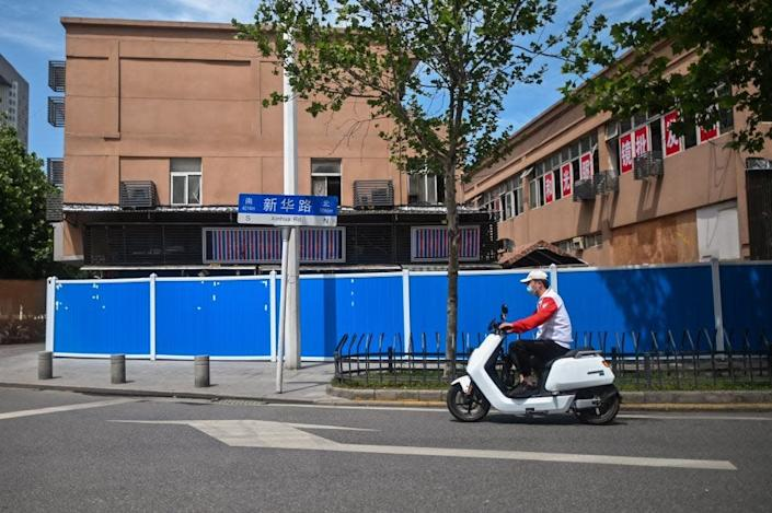 A man rides a scooter past the closed Huanan Seafood Wholesale Market in Wuhan, China, on May 19, 2020.