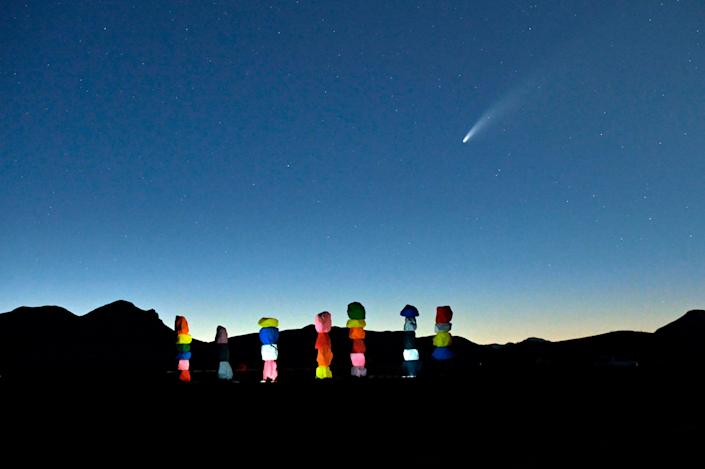 """Comet Neowise is seen in the sky, above the """"Seven Magic Mountains"""" art installation by artist Ugo Rondinone, in Jean, Nevada on July 15, 2020."""