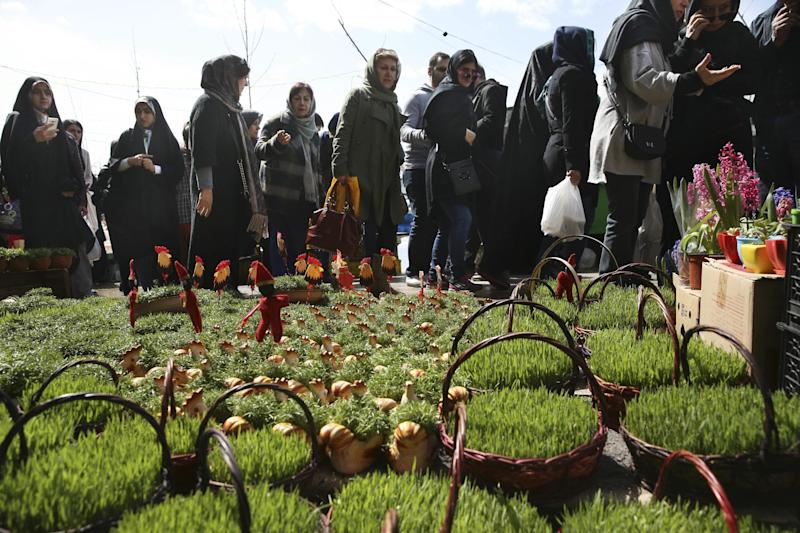 "In this picture taken on Saturday, March 18, 2017, photo, Iranians walk through Tajrish traditional bazaar in northern Tehran, Iran, behind baskets of grass shoots, an item of the Iranian New Year, ahead of the New Year, or Nowruz, meaning ""New Day."" (AP Photo/Vahid Salemi)"