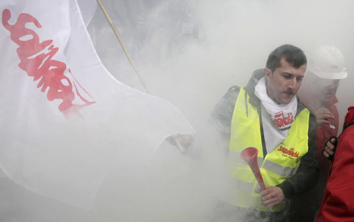 Workers with a Solidarity trade union flag and throwing smoke grenades are protesting a government plan to raise retirement age to 67 outside the in Parliament, in Warsaw, Poland on Friday, March 30, 2012. Prime Minister Donald Tusk says it is necessary to raise the current retirement age of 60 for women and 65 for men in order to cut state budget deficit. (AP Photo/Czarek Sokolowski)