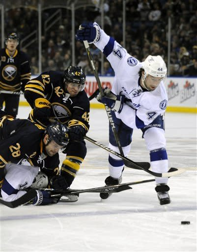 Buffalo Sabres' Paul Gaustad (28) and Nathan Gerbe (42) battle for the puck with Tampa Bay Lightning' Nate Thompson (44) during the first period of an NHL hockey game in Buffalo, N.Y., Saturday, Feb. 11, 2012. (AP Photo/Gary Wiepert)