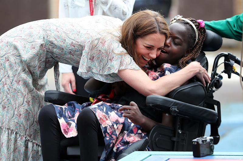 The Duchess of Cambridge hugs Faith Olukoya during a visit to a Royal Photographic Society workshop with Action for Children which uses photography to help young people develop confidence and self-expression, at Warren Park Children's Centre, Kingston upon Thames.