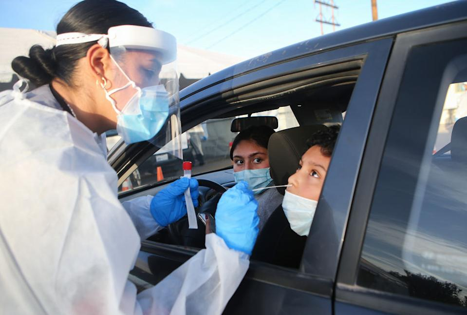 Frontline healthcare worker Joanne Grajeda administers a nasal swab test at a drive-in COVID-19 testing site in Texas. Source: Getty
