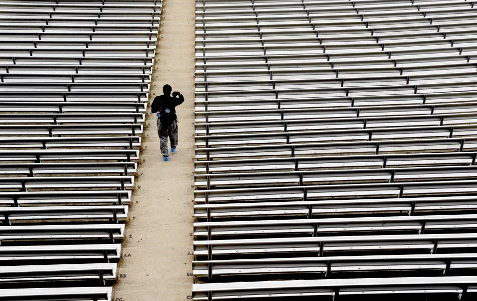 FILE - In this July 16, 2014, file photo, a student walks through empty seats inside Kenan Stadium at the University of North Carolina in Chapel Hill, N.C., where preparations continue for the upcoming college football season. The crippling grip the coronavirus pandemic has had on the sports world has forced universities, leagues and franchises to evaluate how they might someday welcome back fans. (AP Photo/Gerry Broome, File)