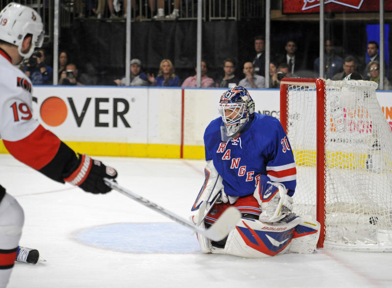 Ottawa Senators' Jason Spezza, left, scores a goal against New York Rangers goaltender Henrik Lundqvist, of Sweden, during the first period of Game 5 of an NHL Stanley Cup first-round hockey playoff series, Saturday, April 21, 2012, at New York's Madison Square Garden. (AP Photo/Bill Kostroun)