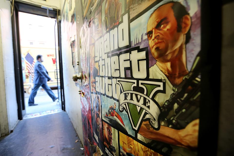 NEW YORK, NY - SEPTEMBER 18:  A poster promoting Grand Theft Auto V is attached to a wall at the 8 Bit & Up video games shop in Manhattan's East Village on September 18, 2013 in New York City. The video game raked in more than $800 million in sales in its first 24 hours on the shelves.  (Photo by Mario Tama/Getty Images)