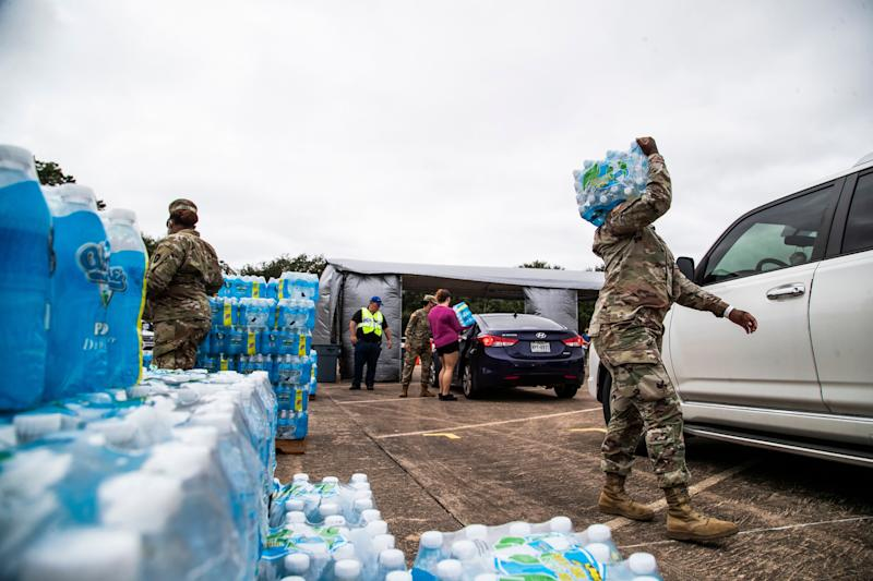National Guard soldiers and local government employees distribute bottled water to residents in Lake Jackson on Monday. Texas Gov. Greg Abbott issued a disaster declaration on Sunday that extends across Brazoria County, where Lake Jackson is located. (Photo: ASSOCIATED PRESS)