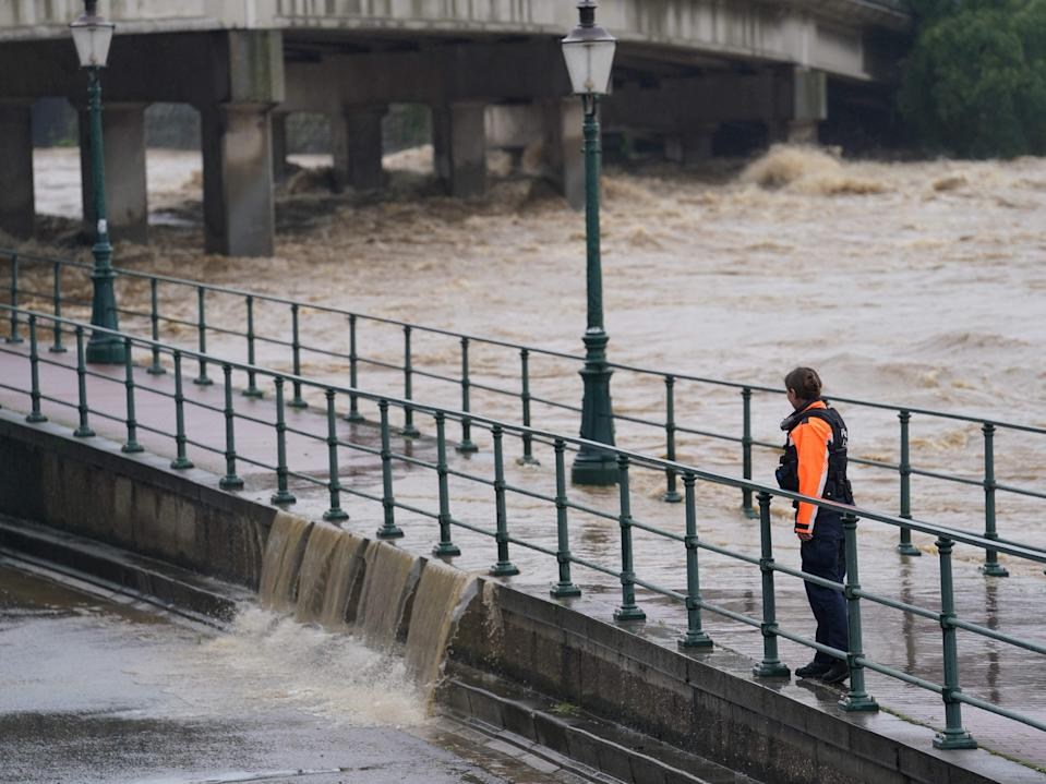 A police officer watches as water from the Meuse river breaches a barrier at the crossing with the Ourthe in Liege (Anthony Dehez/AFP/Getty)