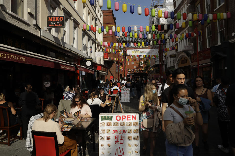 People sit outside on a street closed to traffic to try to reduce the spread of coronavirus so bars, cafes and restaurants can continue to stay open, in the Chinatown area of central London, Saturday, Sept. 19, 2020. Fresh nationwide lockdown restrictions in England appear to be on the cards soon as the British government targeted more areas Friday in an attempt to suppress a sharp spike in new coronavirus infections. (AP Photo/Matt Dunham)