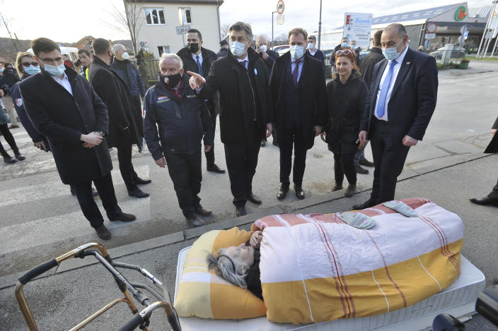 Croatian Prime Minister Andrej Plenkovic, centre, points his finger as he stands next to an elderly woman who was evacuated because of an earthquake, in Petrinja, Croatia, Tuesday, Dec. 29, 2020. A strong earthquake hit Croatia on Tuesday, with some injuries reported as well as considerable damages to roofs and buildings southeast of the capital. (AP Photo)