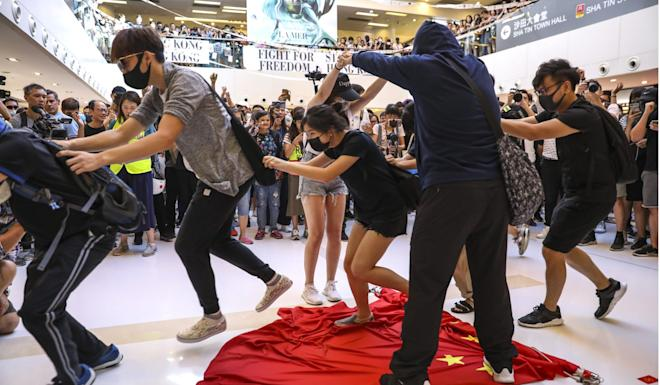 Protesters trample on the Chinese national flag after gathering to protest at New Town Plaza in Sha Tin. Photo: Nora Tam