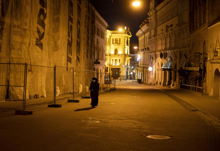 A nun wearing face masks to protect against coronavirus, walks on an empty street in Old Town in Vilnius, Lithuania, Saturday, April 18, 2020. For Orthodox Christians, this is normally a time of reflection, communal mourning and joyful release, of centuries-old ceremonies steeped in symbolism and tradition. But this year, Easter - by far the most significant religious holiday for the world's roughly 300 million Orthodox - has essentially been cancelled. (AP Photo/Mindaugas Kulbis)
