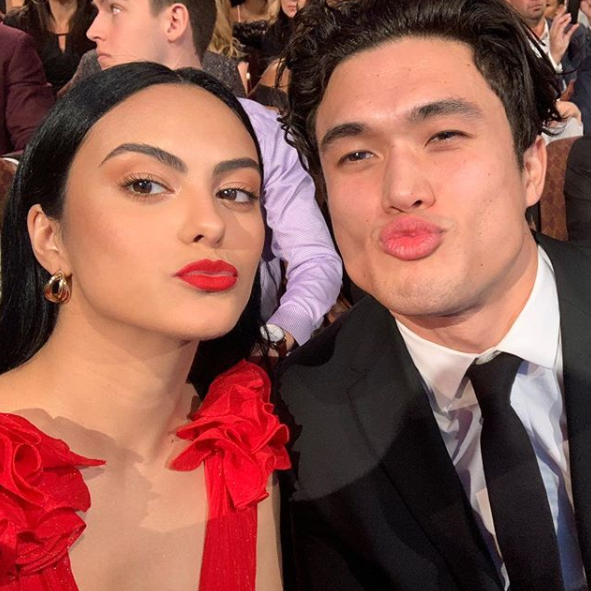 A photo of Riverdale couple Camila Mendes wearing a red dress and Charles Melton wearing a black suit and tie puckering up for a selfie.