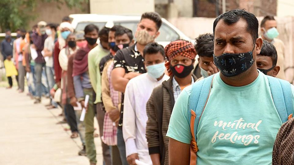 People wait in queue for their turn for COVID-19 testing at a test centre in Jammu, the winter capital of Kashmir, India, 20 April 2021.